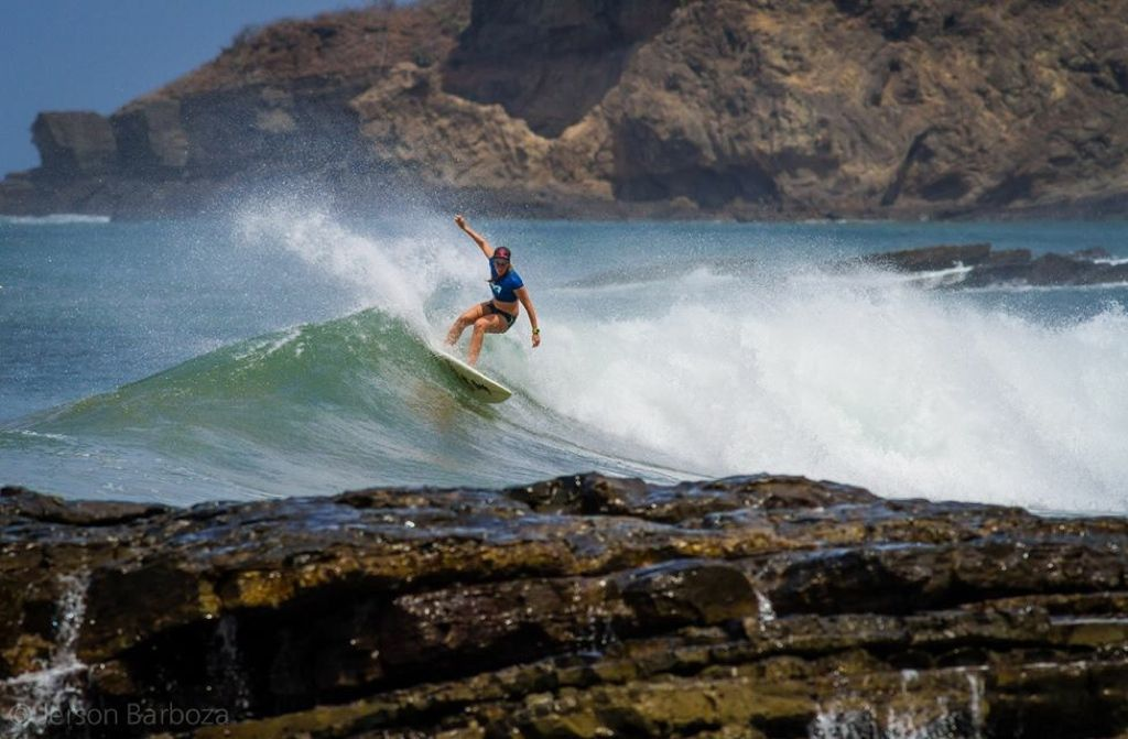 girl surfing on a wave in Nicaragua with cliffs in the background
